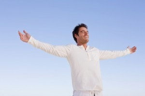 Happy young man with hands out stretched against blue sky