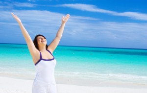 happy woman with raised hands on the beach